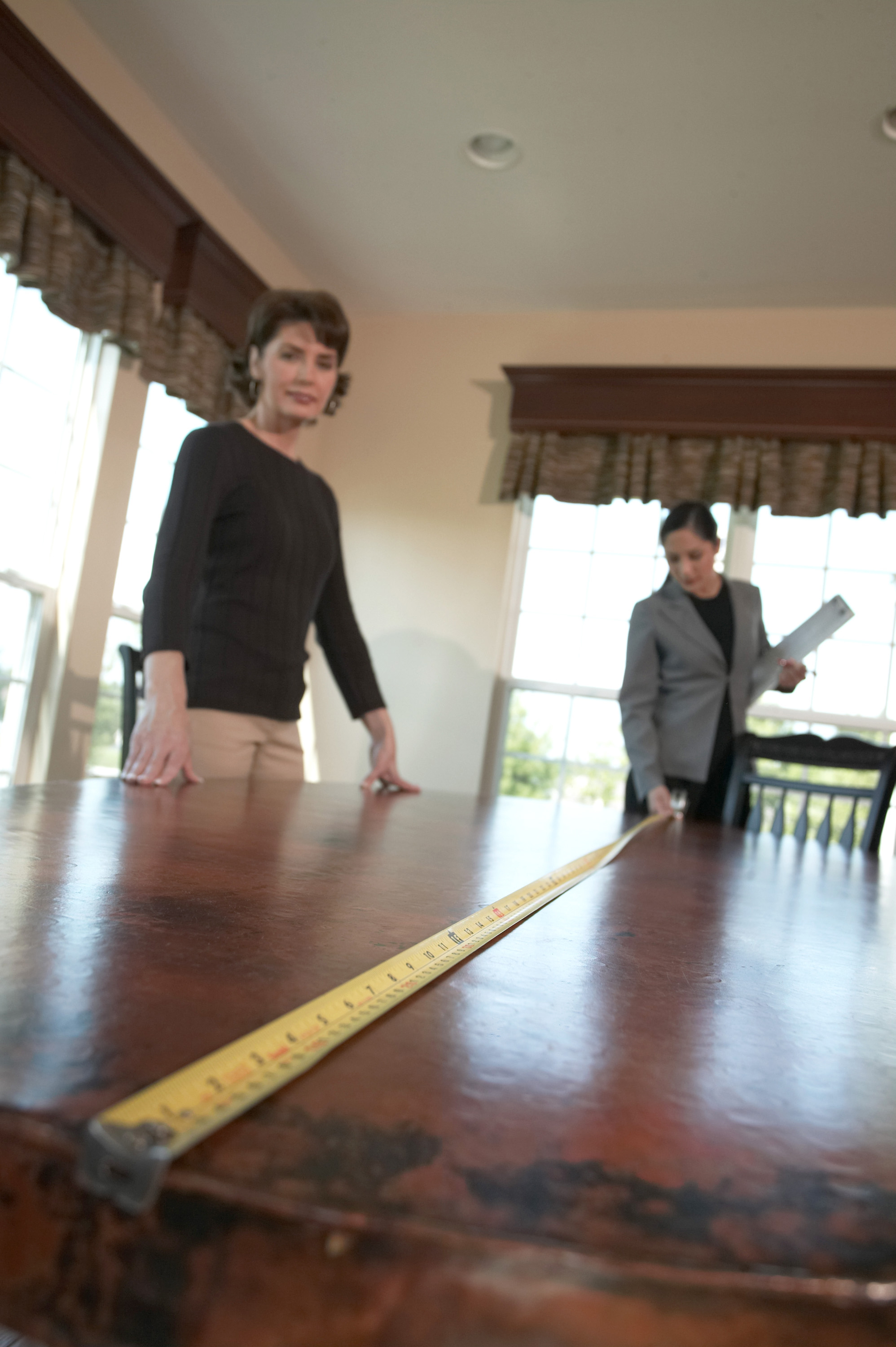 Image of people measuring a table